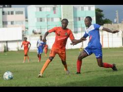 FILE Tivoli's Davian Garrison challenges Ryan Wellington of Portmore United for a loose ball during their RSPL match at the Edward Seaga Sports Complex on Sunday, November 17, 2019.