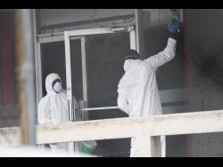 A sanitisation crew cleaning the exterior of the Central Sorting Office building in Kingston in April.