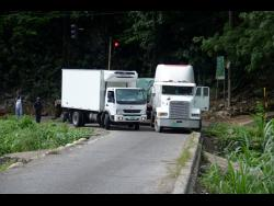 The driver of a small truck navigates his way past the disabled vehicle.