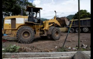 A member of the Jamaica Defence Force mans a tractor as part of the clean-up of sections off Bull Bay.