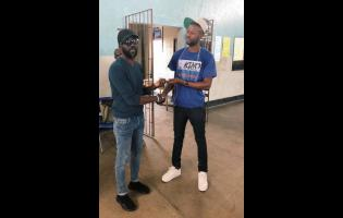 Comedia Ian 'Ity' Ellis (left) fulfils his promise and makes a donation to Akino Page, member of The Dream Team. The money came from proceeds of the Christmas Comedy Cook-Up which was held last month.