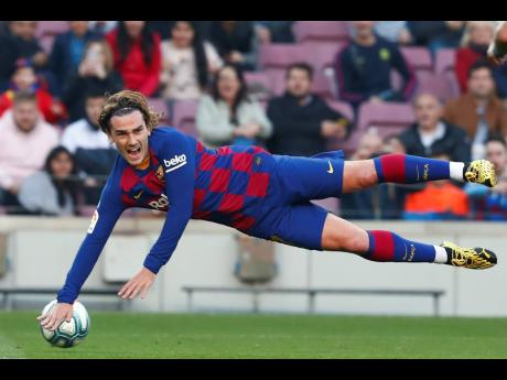 Barcelona's Antoine Griezmann falls during a Spanish La Liga match against Eibar at the Camp Nou stadium in Barcelona, Spain.